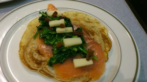 Montando la crepe de espinacas queso y salmon