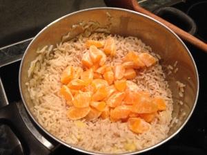 Una vez escurrido y que el arroz haya cogido el gusto de jengibre, le añadimos los gajos de mandarina